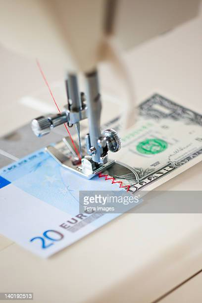Halves of banknotes being sewed with sewing machine