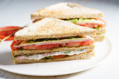 Sandwich of whole wheat bread with ham, cheese and fresh tomato, triangle cut, three layers sandwich bread