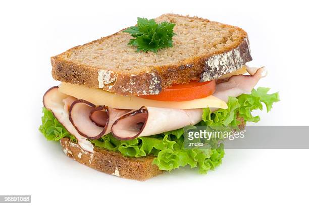 A ham sandwich with lettuce and tomato on wheat bread