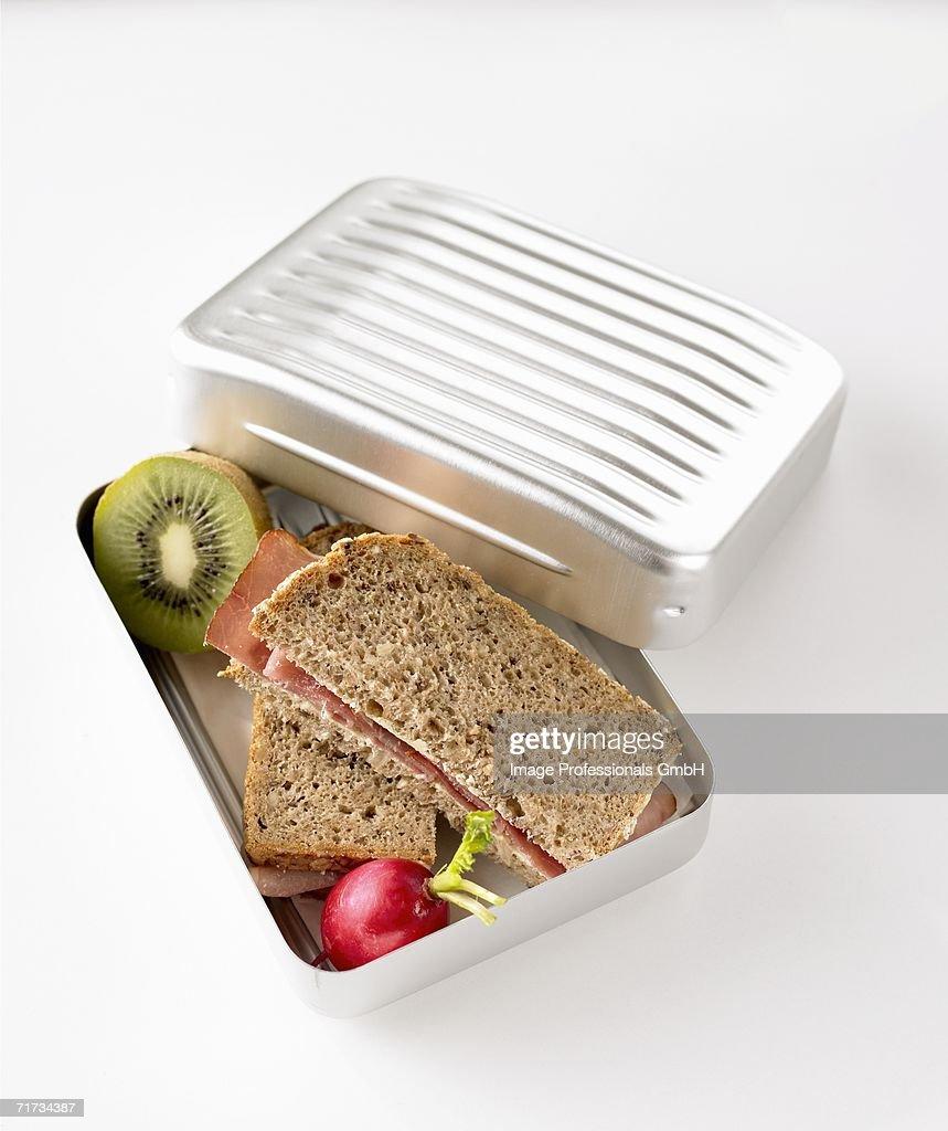 Ham sandwiches, radish and kiwi fruit in lunch box