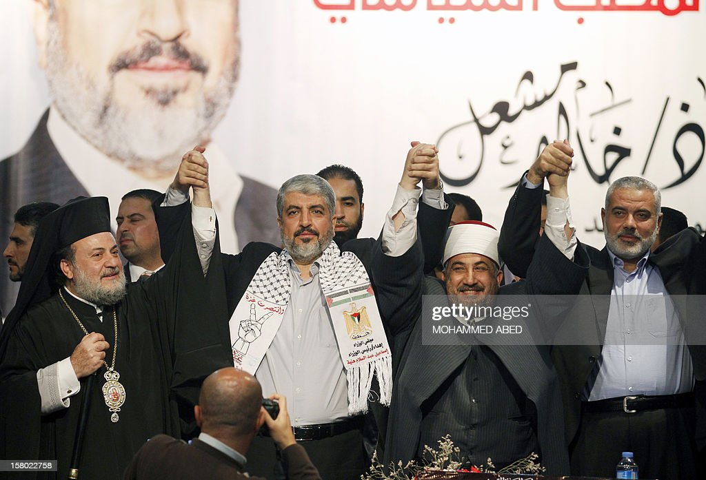 Hamas chief in exile Khaled Meshaal (2nd L) holds hands with Gaza's Greek Orthodox Archbishop Alexios (L) and Hassan al-Jojo (2nd R), president of the Islamic Sharia Appeals Court in Gaza, along with Hamas Prime Minister in the Gaza Strip Ismail Haniya (R), on the third day of Meshaal's visit to Gaza City on December 9, 2012. Meshaal rejected ceding 'an inch' of Palestinian territory to Israel or recognizing the Jewish state, in a speech in Gaza where he is on a historic first visit. AFP PHOTO/MOHAMMED ABED