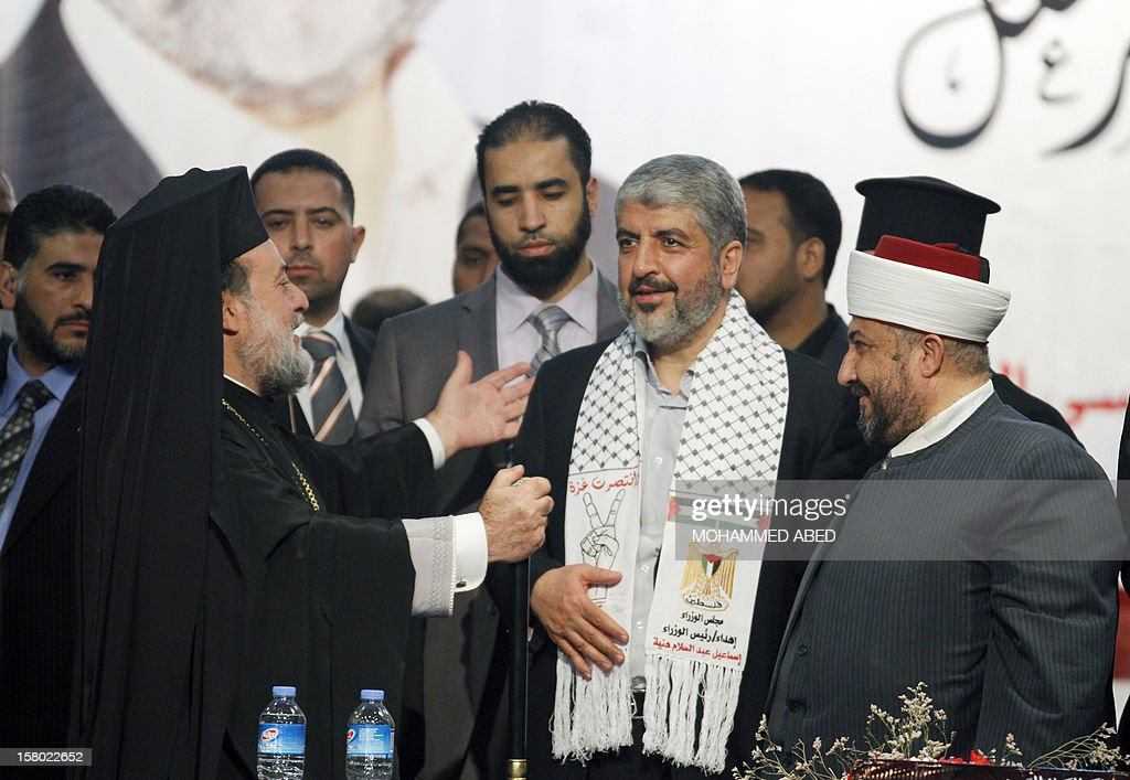 Hamas chief in exile Khaled Meshaal (C) is greeted by Gaza's Greek Orthodox Archbishop Alexios (L) as Hassan Al-Jojo (R), president of the Islamic Sharia Appeals Court in Gaza looks on, during his third day of his visit to Gaza City on December 9, 2012. Meshaal rejected ceding 'an inch' of Palestinian territory to Israel or recognizing the Jewish state, in a speech in Gaza where he is on a historic first visit. AFP PHOTO/MOHAMMED ABED