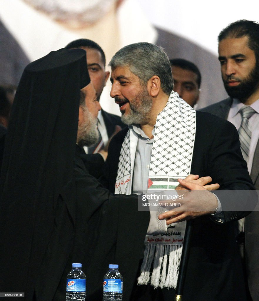 Hamas chief-in-exile Khaled Meshaal (R) greets Gaza's Greek Orthodox Archbishop Alexios on the third day of his visit to Gaza City on December 9, 2012. Meshaal rejected ceding 'an inch' of Palestinian territory to Israel or recognizing the Jewish state, in a speech in Gaza where he is on a historic first visit. AFP PHOTO/MOHAMMED ABED