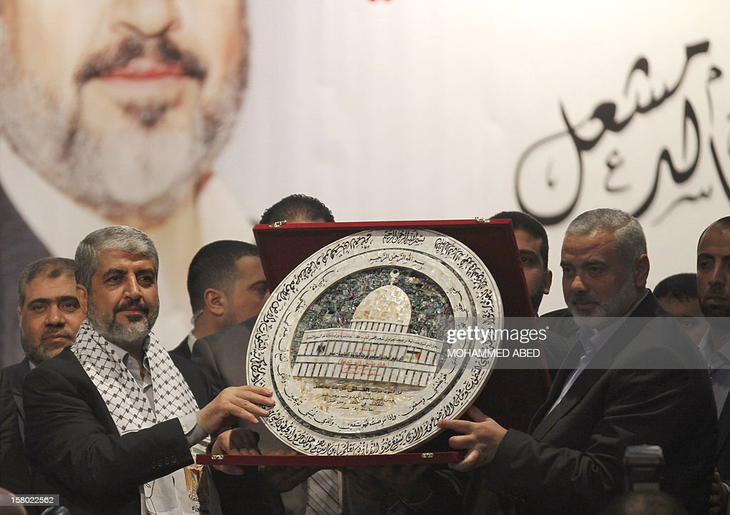 Hamas chief-in-exile Khaled Meshaal (L) receives a scale model of the Dome of the Rock in the Al-Aqsa Mosque Compound in Jerusalem, from Hamas Prime Minister in the Gaza Strip Ismail Haniya (R) during his meeting with the families of people killed during conflict with Israel commonly known as Martyrs, on the third day of his visit to Gaza City, on December 9, 2012. Meshaal reiterated a call for Palestinian unity he made at a rally the day before celebrating the 25th anniversary of the founding of Hamas which rules the Gaza Strip.