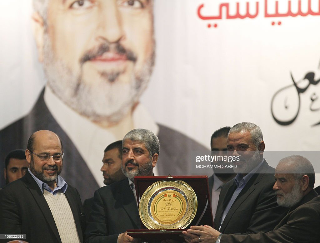 Hamas chief-in-exile Khaled Meshaal (2nd L) receives a scale model of the Dome of the Rock in the Al-Aqsa Mosque Compound in Jerusalem, from Hamas Prime Minister in the Gaza Strip Ismail Haniya (2nd R) during his meeting with the families of people killed during conflict with Israel commonly known as Martyrs, on the third day of his visit to Gaza City, on December 9, 2012. Meshaal reiterated a call for Palestinian unity he made at a rally the day before celebrating the 25th anniversary of the founding of Hamas which rules the Gaza Strip.