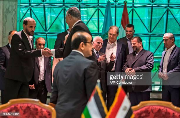 Hamas' Hussam Badran shakes hands with Khaled Fawzi the head of the Egyptian intelligence services while the chief of Fatah's delegation Azzam...