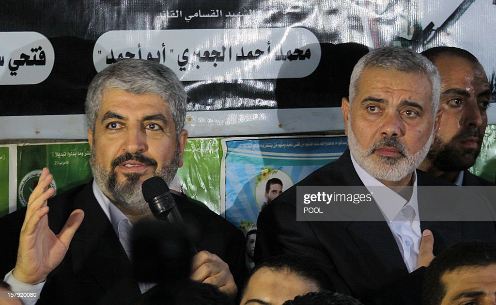 Hamas leader in exile Khaled Meshaal (L) addresses Hamas supporters as he stands next to Gaza's Hamas prime minister Ismail Haniya (R) during their visit to the house of Ahmed Jaabari, the late leader of the Hamas armed wing who was killed in an Israeli air strike last month, in Gaza City on December 7, 2012. Meshaal made his first visit to Gaza, kissing the ground and saying he hoped he would one day die a 'martyr' in the Palestinian territory. AFP PHOTO/POOL/MOHAMMED SABER