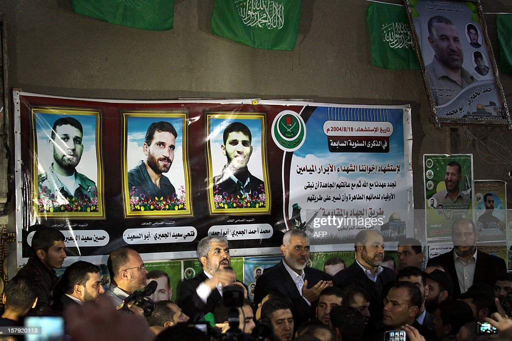 Hamas leader in exile Khaled Meshaal (C-L) addresses Hamas supporters as he stands next to Gaza's Hamas prime minister Ismail Haniya (C-R) during their visit to the house of Ahmed Jaabari, the late leader of the Hamas armed wing who was killed in an Israeli air strike last month, in Gaza City on December 7, 2012. Meshaal made his first visit to Gaza, kissing the ground and saying he hoped he would one day die a 'martyr' in the Palestinian territory.