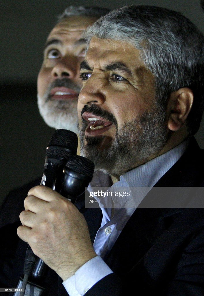 Hamas leader in exile Khaled Meshaal addresses the crowd during a visit to Al-Dallu family, of which 10 members were killed in an Isareli air strike during Israel's eight-day Operation Pillar of Defence, in Gaza City on December 7, 2012. Meshaal made his first visit to Gaza, kissing the ground and saying he hoped he would one day die a 'martyr' in the Palestinian territory. AFP PHOTO/POOL/HATEM MOUSSA