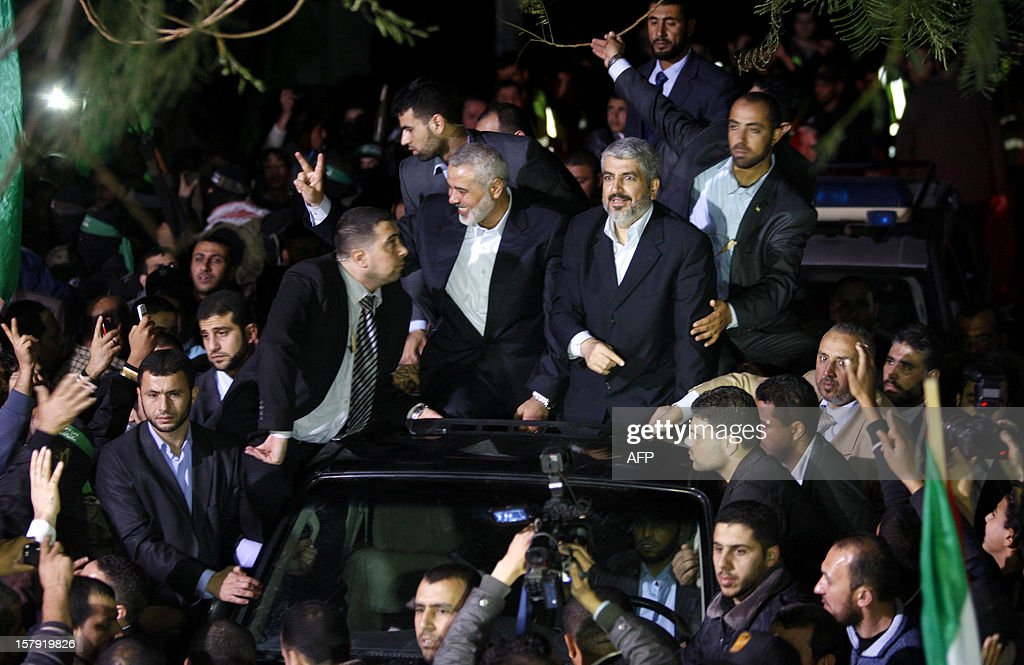 Hamas leader in exile Khaled Meshaal (C-R) and Gaza's Hamas prime minister Ismail Haniya (C-L) arrive for a visit to Al-Dallu family, of which 10 members were killed in an Isareli air strike during Israel's eight-day Operation Pillar of Defence, in Gaza City on December 7, 2012. Meshaal made his first visit to Gaza, kissing the ground and saying he hoped he would one day die a 'martyr' in the Palestinian territory. AFP PHOTO/POOL/HATEM MOUSSA