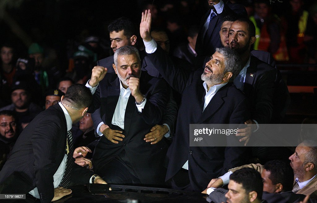Hamas leader in exile Khaled Meshaal (C-R) and Gaza's Hamas prime minister Ismail Haniya (C-L) arrive for a visit to Al-Dallu family, of which 10 members were killed in an Isareli air strike during Israel's eight-day Operation Pillar of Defence, in Gaza City on December 7, 2012. Meshaal made his first visit to Gaza, kissing the ground and saying he hoped he would one day die a 'martyr' in the Palestinian territory.
