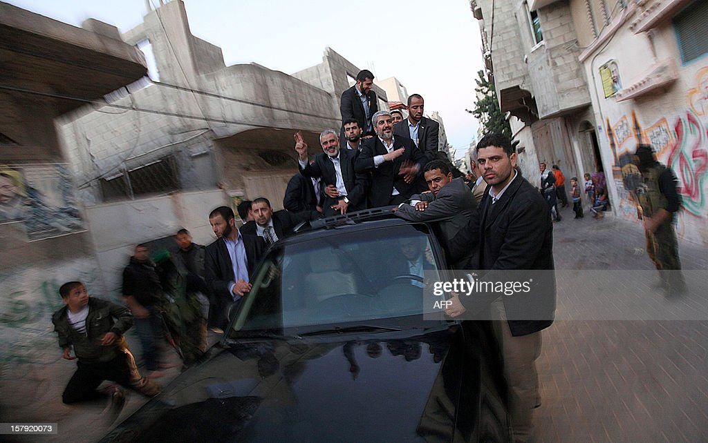 Hamas leader in exile Khaled Meshaal (C-R) and Gaza's Hamas prime minister Ismail Haniya (C-L) gesture at Hamas supporters as they arrive for a visit to the house of Ahmed Jaabari, the late leader of the Hamas armed wing who was killed in an Israeli air strike last month, in Gaza City on December 7, 2012. Meshaal made his first visit to Gaza, kissing the ground and saying he hoped he would one day die a 'martyr' in the Palestinian territory.