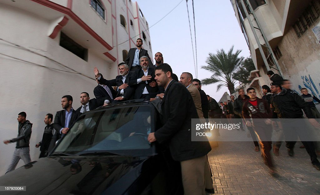 Hamas leader in exile Khaled Meshaal (C) and Gaza's Hamas prime minister Ismail Haniya (C-L) gesture at Hamas supporters as they arrive for a visit to the house of Ahmed Jaabari, the late leader of the Hamas armed wing who was killed in an Israeli air strike last month, in Gaza City on December 7, 2012. Meshaal made his first visit to Gaza, kissing the ground and saying he hoped he would one day die a 'martyr' in the Palestinian territory. AFP PHOTO/POOL/MOHAMMED SABER