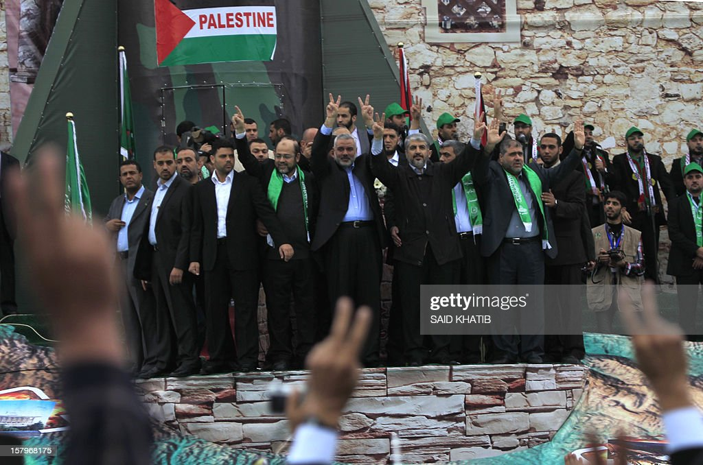 Hamas leader in exile Khaled Meshaal (C-R) and Hamas prime minister in the Gaza strip Ismail Haniya (C-L) flash the V-sign for victory to supporter during a rally to mark the 25th anniversary of the founding of the Islamist movement, in Gaza on December 8, 2012. Hamas leader in exile Khaled Meshaal made his first visit to Gaza, timed to coincide with the 25th anniversary of the Islamist movement's founding.