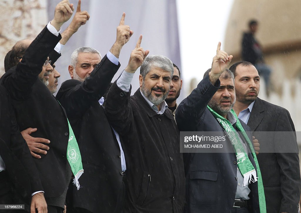 Hamas leader in exile Khaled Meshaal (C) and Hamas prime minister in the Gaza Strip Ismail Haniya (C-L) gesture to the crowd during a rally in Gaza City on December 8, 2012, to mark the 25th anniversary of the founding of the Islamist movement. More than 100,000 Palestinians gathered in Gaza for the rally to mark the occasion during which Meshaal delivered a speech. AFP PHOTO/MOHAMMED ABED