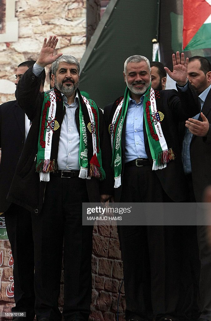 Hamas leader in exile Khaled Meshaal (L) and Hamas prime minister in the Gaza strip Ismail Haniya (R) wave to Palestinian supporters during a rally in Gaza on December 8, 2012, to mark the 25th anniversary of the founding of the Islamist movement. More than 100,000 Palestinians gathered in Gaza for the rally to mark the occasion during which Meshaal delivered a speech. AFP PHOTO/ MAHMUD HAMS