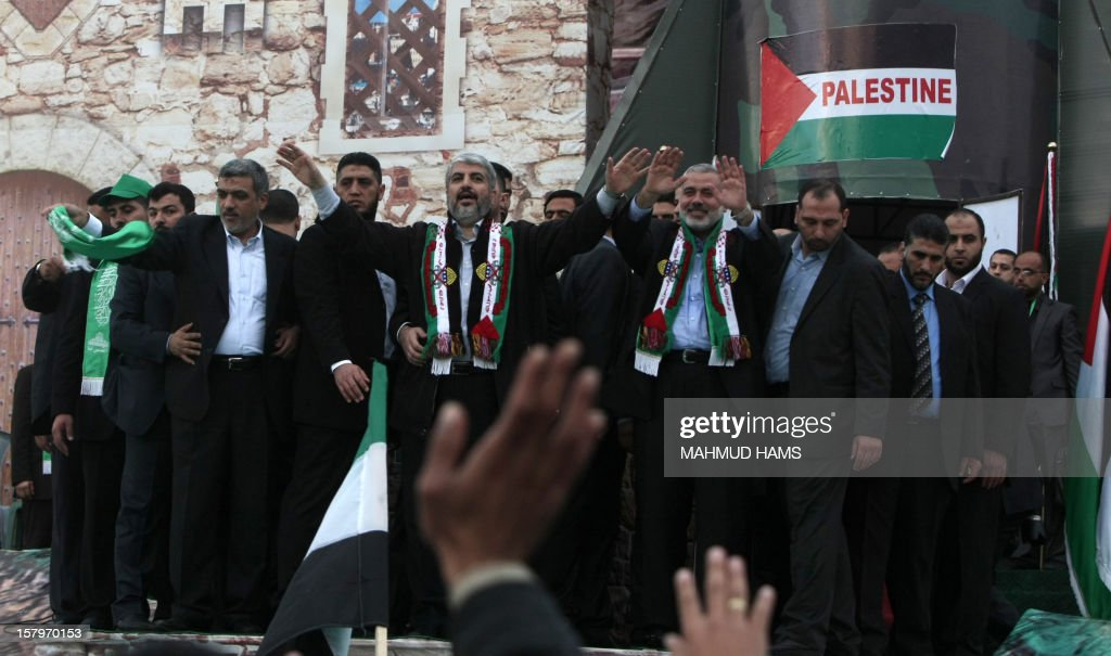 Hamas leader in exile Khaled Meshaal (C-L) and Hamas prime minister in the Gaza strip Ismail Haniya (C-R) wave to Palestinian supporters during a rally in Gaza City on December 8, 2012, to mark the 25th anniversary of the founding of the Islamist movement. More than 100,000 Palestinians gathered in Gaza for the rally to mark the occasion during which Meshaal delivered a speech.