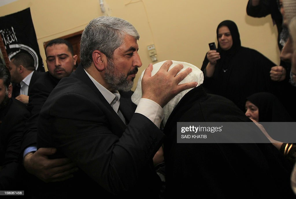 Hamas leader in exile Khaled Meshaal kisses the head of the mother of Kamal al-Nayrab, the killed leader of the Popular Resistance Committees, on December 10, 2012 in Rafah, southern Gaza Strip. Exiled Hamas chief Khaled Meshaal left Gaza after a historic first visit to the tiny Palestinian enclave. AFP PHOTO/ SAID KHATIB