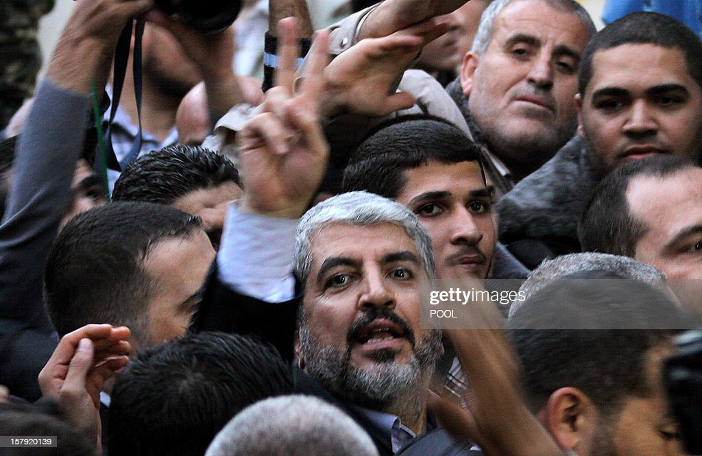 Hamas leader in exile Khaled Meshaal makes the victory sign upon arrival to visit the house of Ahmed Jaabari, the late leader of the Hamas armed wing who was killed in an Israeli air strike last month, in Gaza City on December 7, 2012. Meshaal made his first visit to Gaza, kissing the ground and saying he hoped he would one day die a 'martyr' in the Palestinian territory.
