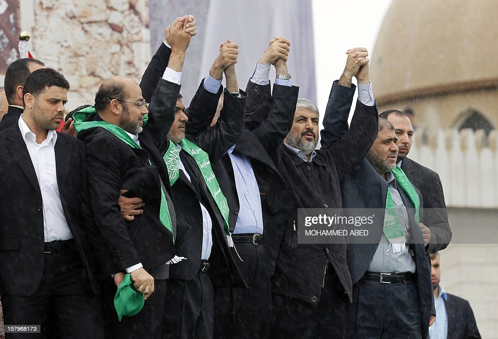 Hamas leader in exile Khaled Meshaal (3R) raises his hands to the crowd during a rally in Gaza City on December 8, 2012, to mark the 25th anniversary of the founding of the Islamist movement. More than 100,000 Palestinians gathered in Gaza for the rally to mark the occasion during which Meshaal delivered a speech. AFP PHOTO/MOHAMMED ABED