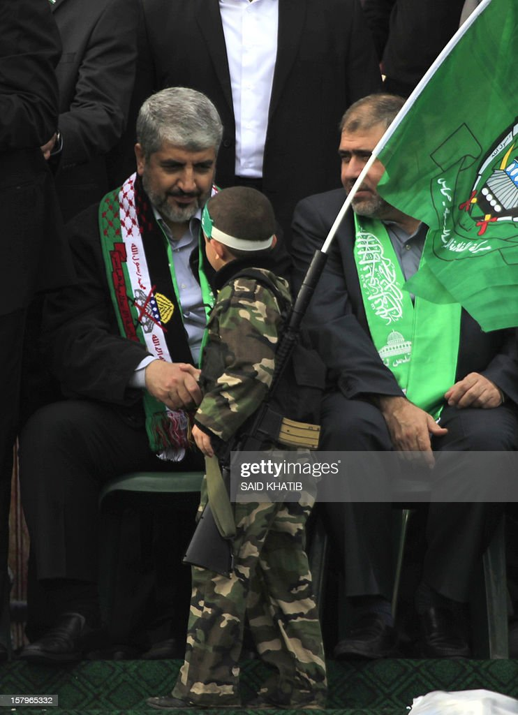 Hamas leader in exile Khaled Meshaal Shake hand with a boy during a rally to mark the 25th anniversary of the founding of the Islamist movement, in Gaza City on December 8, 2012. Meshaal made his first visit to Gaza, timed to coincide with the 25th anniversary of the Islamist movement's founding.