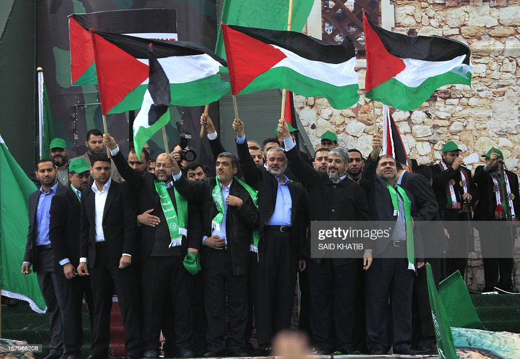 Hamas leader in exile Khaled Meshaal (2nd C-R) stands next to Hamas prime minister in the Gaza strip Ismail Haniya (5th-L) as they wave the Palestinian flag during a rally to mark the 25th anniversary of the founding of the Islamist movement, in Gaza on December 8, 2012. Meshaal made his first visit to Gaza, timed to coincide with the 25th anniversary of the Islamist movement's founding.