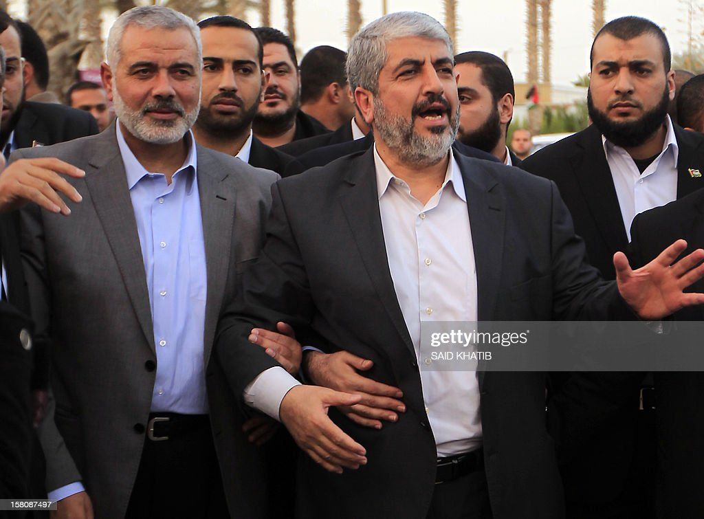 Hamas leader in exile Khaled Meshaal (R) waves goodbye while standing next to Hamas prime minister in the Gaza Strip Ismail Haniya (L) upon his departure from the Gaza Strip on December 10, 2012 in Rafah, on the border with Egypt. Exiled Hamas chief Khaled Meshaal left Gaza after a historic first visit to the tiny Palestinian enclave. AFP PHOTO/ SAID KHATIB