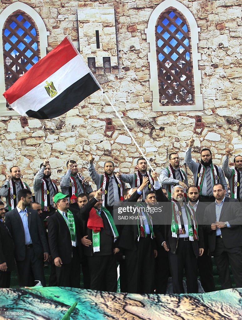 Hamas leader in exile Khaled Meshaal (3rd R) waves the Egyptian flag during a rally to mark the 25th anniversary of the founding of the Islamist movement, in Gaza City on December 8, 2012. Meshaal made his first visit to Gaza, timed to coincide with the 25th anniversary of the Islamist movement's founding.