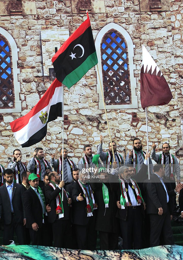 Hamas leader in exile Khaled Meshaal (2nd R) waves the Libyan flag (C) and Qatari flag (R) as a comrade holds up the Egyptian flag (L) during a rally to mark the 25th anniversary of the founding of the Islamist movement, in Gaza City on December 8, 2012. Meshaal made his first visit to Gaza, timed to coincide with the 25th anniversary of the Islamist movement's founding. Hamas prime minister in the Gaza Strip Ismail Haniya is seen (4th L).