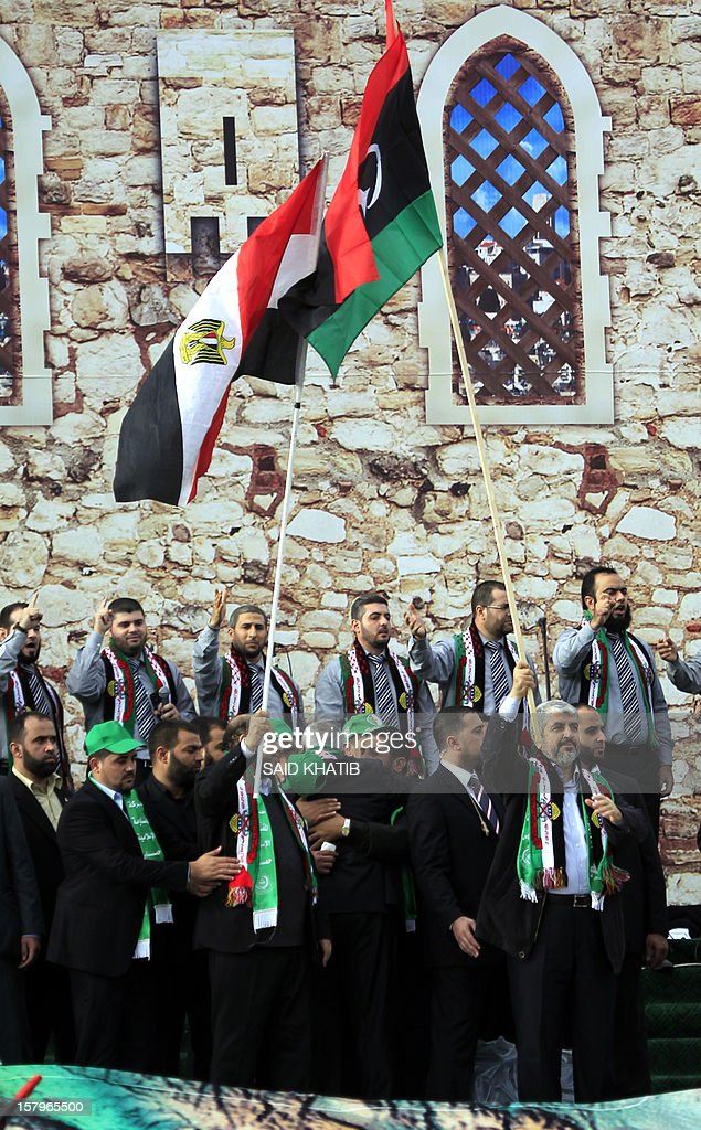 Hamas leader in exile Khaled Meshaal (R) waves the Libyan flag during a rally to mark the 25th anniversary of the founding of the Islamist movement, in Gaza City on December 8, 2012. Meshaal made his first visit to Gaza, timed to coincide with the 25th anniversary of the Islamist movement's founding. AFP PHOTO/ SAID KHATIB