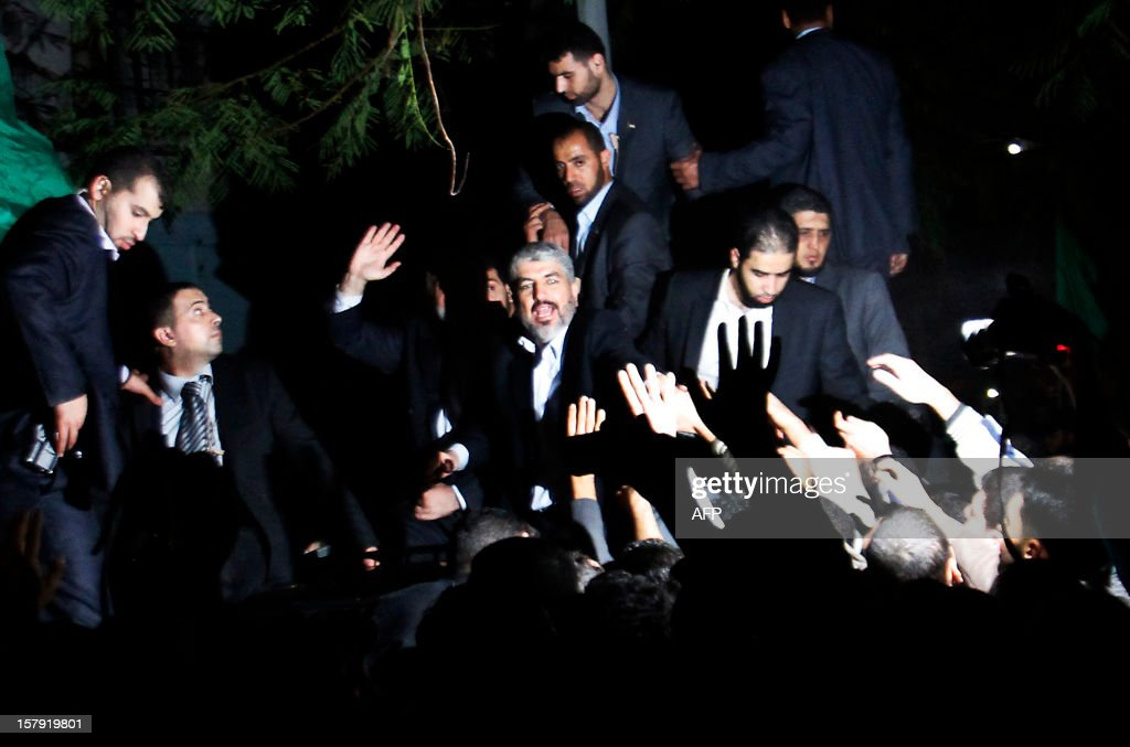 Hamas leader in exile Khaled Meshaal (C) waves to the crowd during a visit to Al-Dallu family, of which 10 members were killed in an Isareli air strike during Israel's eight-day Operation Pillar of Defence, in Gaza City on December 7, 2012. Meshaal made his first visit to Gaza, kissing the ground and saying he hoped he would one day die a 'martyr' in the Palestinian territory. AFP PHOTO/POOL/HATEM MOUSSA