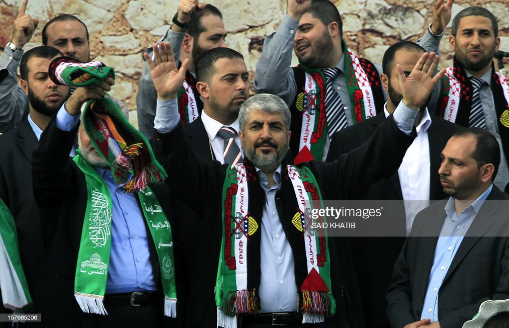 Hamas leader in exile Khaled Meshaal (C) waves to the crowds as Hamas prime minister in the Gaza Strip Ismail Haniya (L) stands by, during a rally to mark the 25th anniversary of the founding of the Islamist movement, in Gaza City on December 8, 2012. Meshaal made his first visit to Gaza, timed to coincide with the 25th anniversary of the Islamist movement's founding. AFP PHOTO/ SAID KHATIB