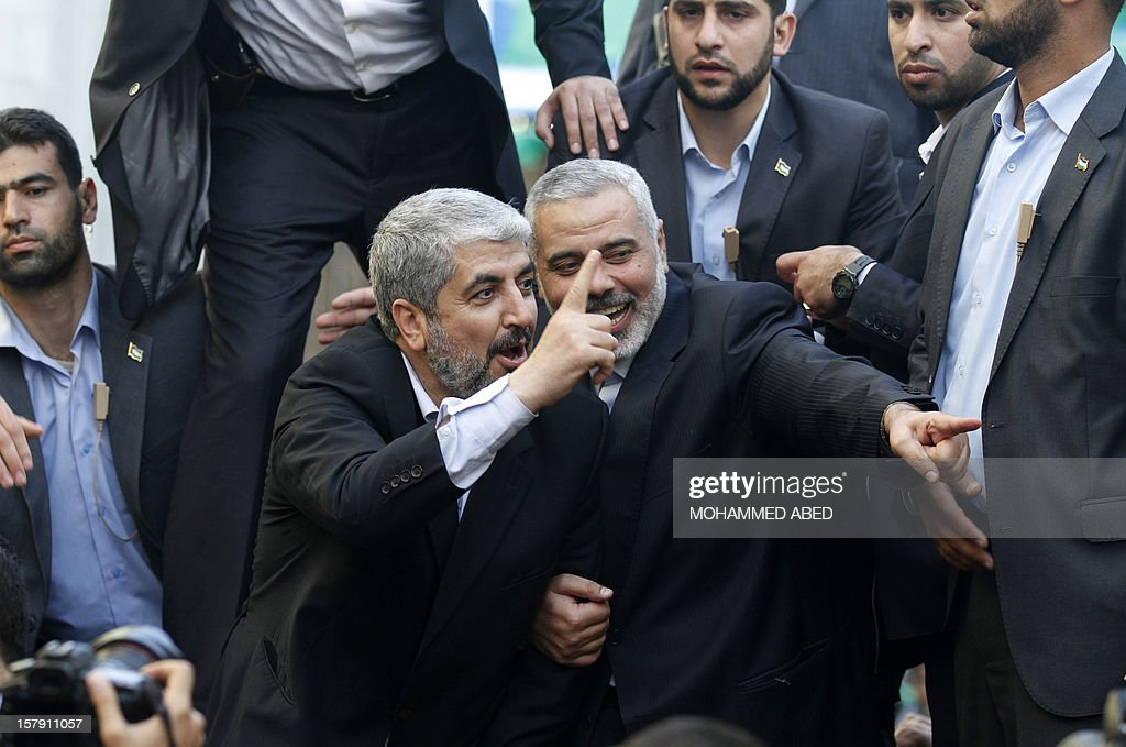 Hamas leader-in-exile Khaled Meshaal (C-L) and Hamas leader in the Gaza Strip Ismail Haniya (C-R) wave from the rooftop of a vehicle during a parade following Meshaal's arrival in Gaza City, on December 7, 2012. Meshaal is making his first-ever visit to the Gaza Strip amid tight security for festivities marking the ruling Islamist movement's 25th anniversary. AFP PHOTO/MOHAMMED ABED