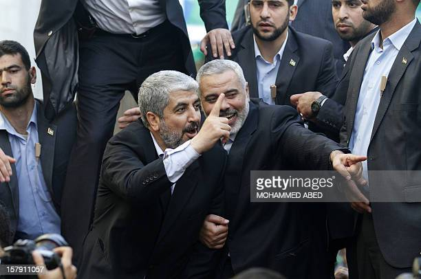 Hamas leaderinexile Khaled Meshaal and Hamas leader in the Gaza Strip Ismail Haniya wave from the rooftop of a vehicle during a parade following...