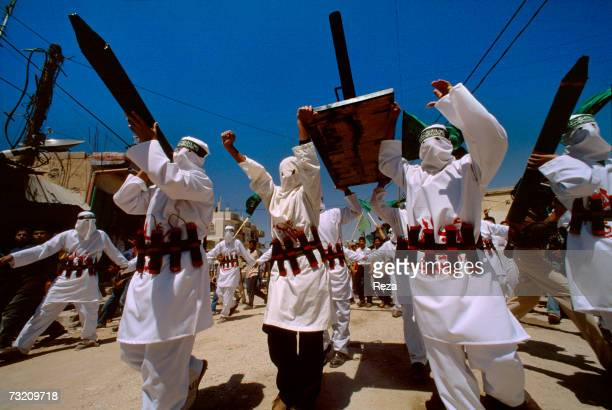 Hamas militants carrying replica rockets and wearing replica bombs wrapped around their waist parade down a street during a protest in Jabaliya's...