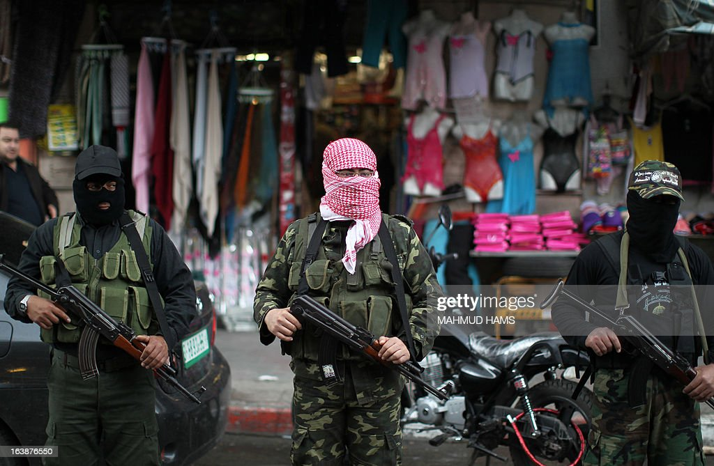 Hamas militants hold weapons during the funeral procession for Hamas militant and lawmaker Mariam Farahat in Gaza City on March 17, 2013. Farhat, who was known for losing three of her militant sons to suicide bombings and Israeli military attacks, died after a long-term illness. AFP PHOTO MAHMUD HAMS