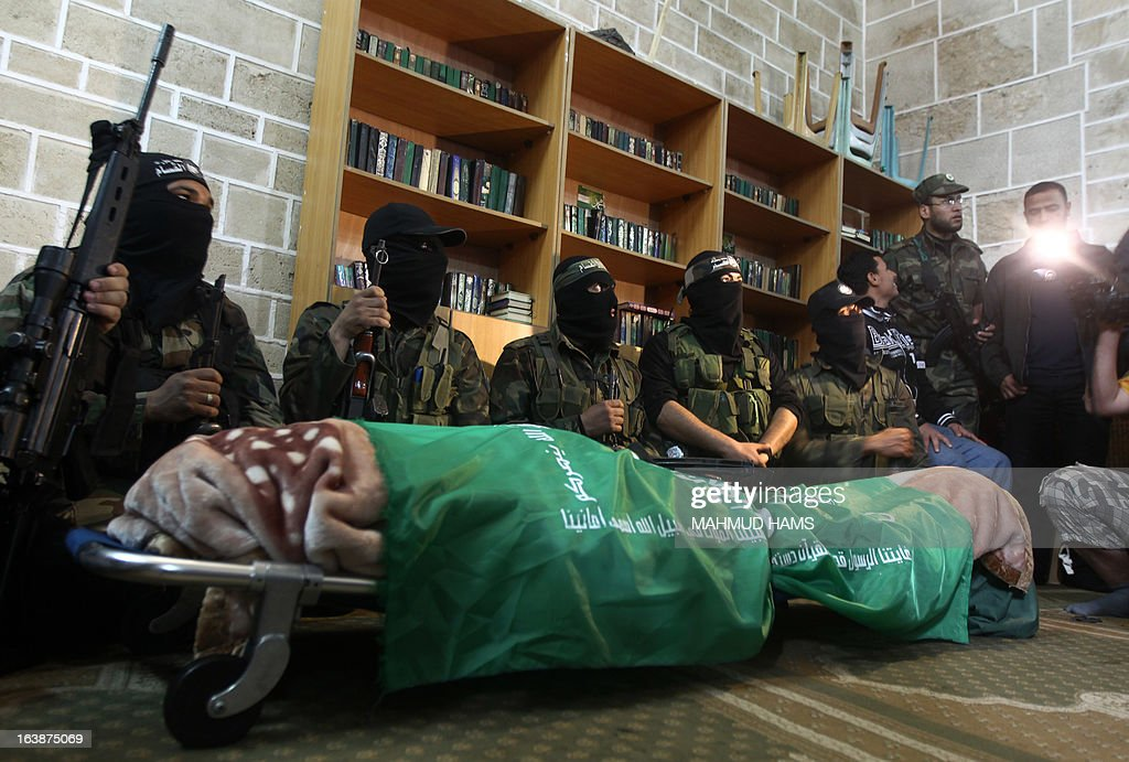 Hamas militants surround the body of a Hamas militant, lawmaker Mariam Farahat during her funeral at al-Omari Mosque in Gaza City on March 17, 2013. Farhat, who was known for losing three of her militant sons to suicide bombings and Israeli military attacks, died after a long-term illness. AFP PHOTO MAHMUD HAMS