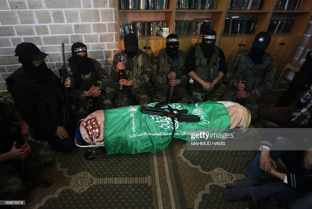 Hamas militants surround the body of a Hamas militant, lawmaker Mariam Farahat during her funeral at al-Omari Mosque in Gaza City on March 17, 2013. Farhat, who was known for losing three of her militant sons to suicide bombings and Israeli military attacks, died after a long-term illness.