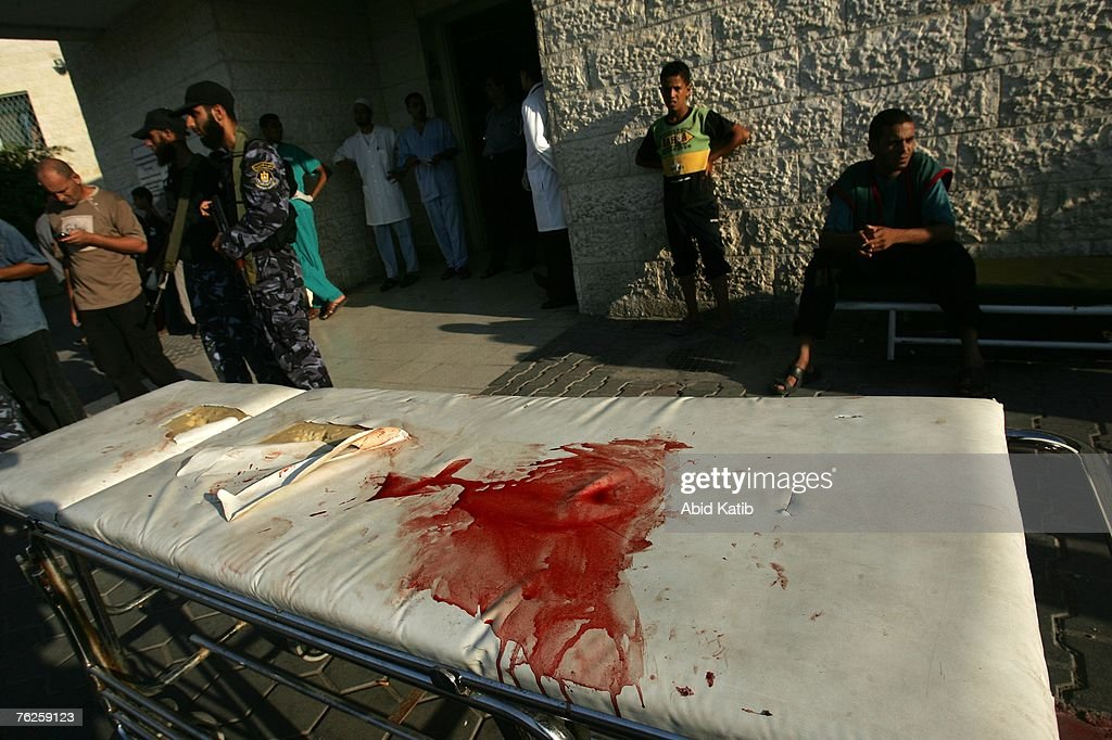 Hamas militia stand guard next to a stretcher covered in blood from a casualty of an Israeli air strike on August 20 2007 in AlBurej Gaza