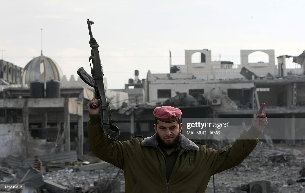 A Hamas policeman celebrates after his return to the Palestinian movement's destroyed Al-Saraya headquarters in Gaza City November 22, 2012, a day after a cease fire was declared. An Egypt-brokered truce took hold in the Gaza Strip after a week of bitter fighting between militant groups and Israel, with both sides claiming victory but remaining wary. AFP PHOTO/MAHMUD HAMS