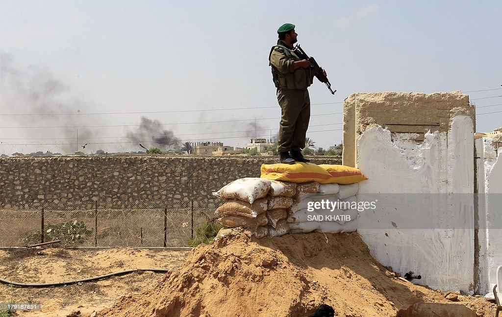 A Hamas policeman stand on sand bags along the border with Egypt on September 1, 2013 in Rafah in the southern Gaza Strip, as smoke rises (L) in the Egyptian side of the border following an explosion at a smuggling tunnel dug beneath the Gaza-Egypt border. Egyptian security forces have stepped up a crackdown campaign on smuggling tunnels between Egypt and the Gaza Strip since July, Hamas officials said. AFP PHOTO SAID KHATIB