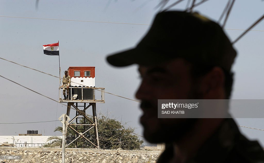 A Hamas policeman (R) stands in Rafah in the southern Gaza Strip on the border with Egypt, on July 5, 2013 while an Egyptian soldier standing on top of a watch tower keeps watch from the Egyptian side of the border. An Egyptian soldier was killed early today in coordinated rocket and machinegun attacks by Islamist militants on army checkpoints and a police base in the restive Sinai, medics said.