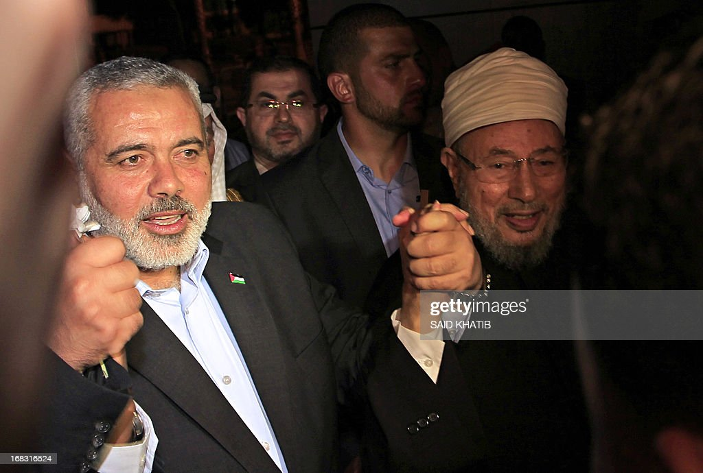 Hamas Prime Minister Ismail Haniyeh (L) holds the hand of Egyptian Cleric and chairman of the International Union of Muslim Scholars Sheikh Yusuf al-Qaradawi (R) upon al-Qaradawi's arrival at Rafah Crossing in the southern Gaza Strip May 8, 2013. Al-Qaradawi arrived on May 8, 2013 for a three-day visit to Gaza Strip with a delegation of Muslim scholars.