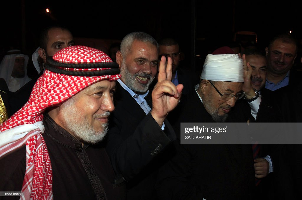 Hamas Prime Minister Ismail Haniyeh (2ndL) makes the V-Victory sign next to Egyptian Cleric and chairman of the International Union of Muslim Scholars Sheikh Yusuf al-Qaradawi (2ndR) upon al-Qaradawi's arrival at Rafah Crossing in the southern Gaza Strip May 8, 2013. Al-Qaradawi arrived on May 8, 2013 for a three-day visit to Gaza Strip with a delegation of Muslim scholars.