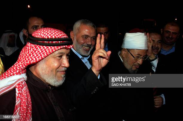 Hamas Prime Minister Ismail Haniyeh makes the VVictory sign next to Egyptian Cleric and chairman of the International Union of Muslim Scholars Sheikh...