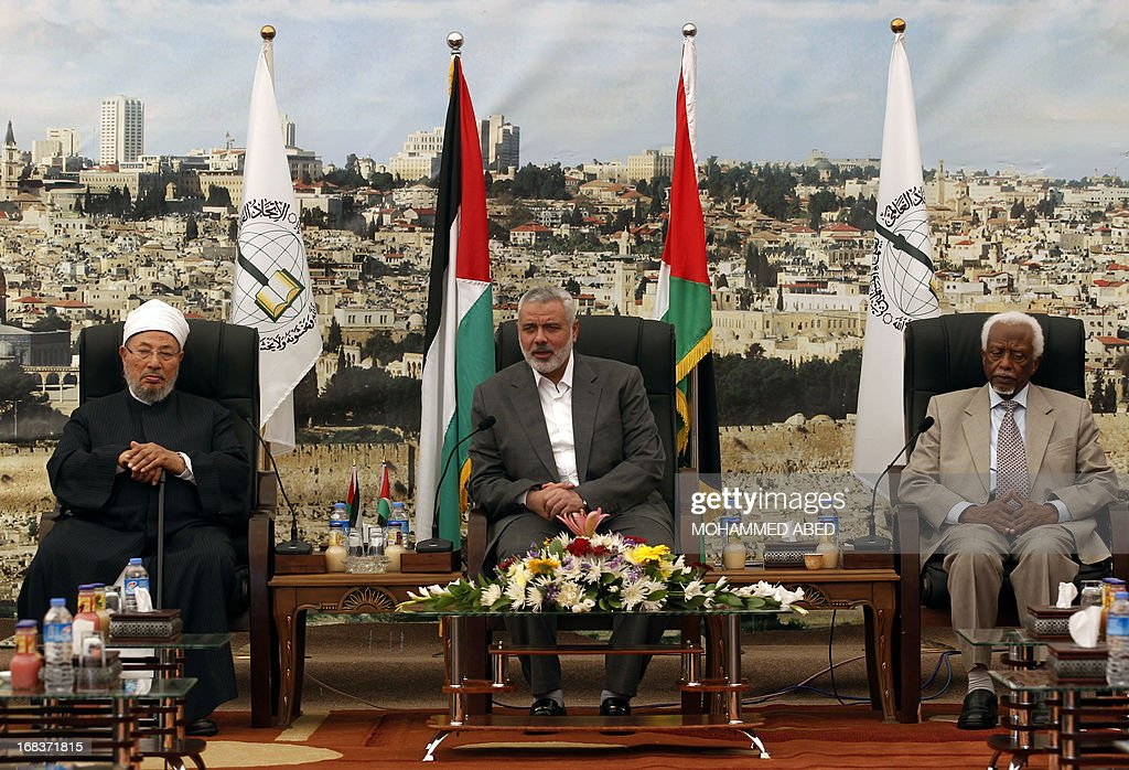 Hamas Prime Minister Ismail Haniyeh (C) meets with Egyptian Cleric and chairman of the International Union of Muslim Scholars Sheikh Yusuf al-Qaradawi (L) and former Sudanese president Abdel Rahman Swar Al Dahab (R) after their arrival in Gaza City on May 9, 2013. Al-Qaradawi arrived on May 8, 2013 for his first visit to Gaza Strip with a delegation of Muslim scholars.