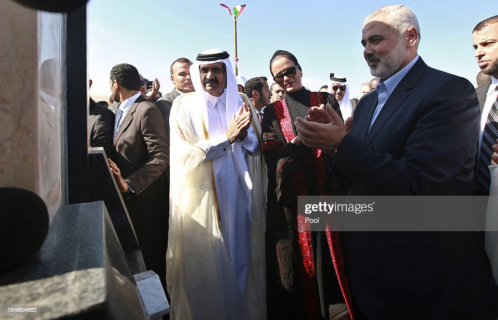 Hamas Prime Minister <a gi-track='captionPersonalityLinkClicked' href=/galleries/search?phrase=Ismail+Haniyeh&family=editorial&specificpeople=543410 ng-click='$event.stopPropagation()'>Ismail Haniyeh</a> (R) of the Palestinian National Authority, the Emir of Qatar Sheikh Hamad bin Khalifa al-Thani (L) and his wife Sheikha Mozah bint Nasser al-Missned (C) attend a cornerstone-laying ceremony for Hamad, a new residential neighbourhood October 23, 2012 in Khan Younis in the southern Gaza Strip. The Emir of Qatar embraced the Hamas leadership of Gaza with an official visit, breaking the isolation of the militant Palestinian Islamist movement, to the dismay of Israel and rival, Western-backed Palestinian leaders in the West Bank.