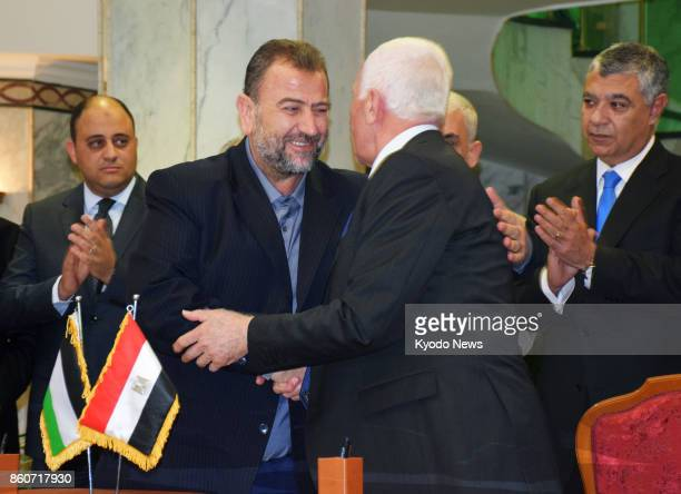 Hamas' Saleh alArouri and Azzam alAhmad of Fatah shake hands in Cairo on Oct 12 as the two rival Palestinian factions reached a reconciliation...