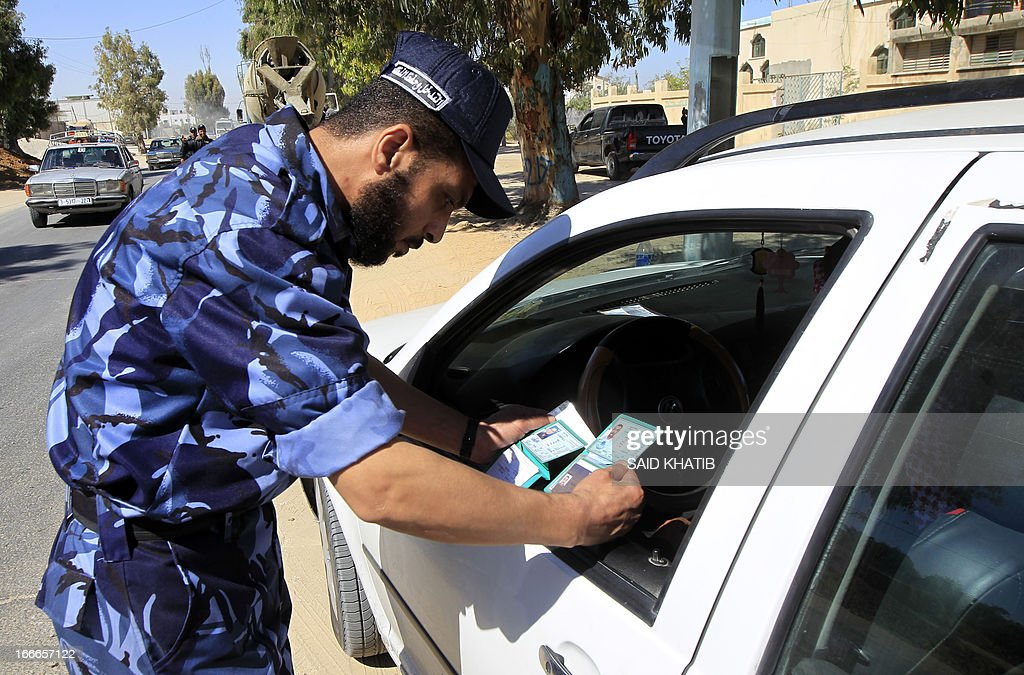 A Hamas security officers looks at IDs after stopping a car at a checkpoint on the outskirts of the border between Rafah town in the southern Gaza strip and Israel to prevent any Palestinian collaborators from escaping into Israel on April 15, 2013. Hamas accused Western and Arab spy agencies of operating in the Gaza Strip and said it had a list of alleged collaborators. Security forces in the Hamas-ruled Gaza Strip have started arresting suspected 'collaborators' with Israel after a month-long amnesty ended, a Hamas official said. AFP PHOTO/SAID KHATIB