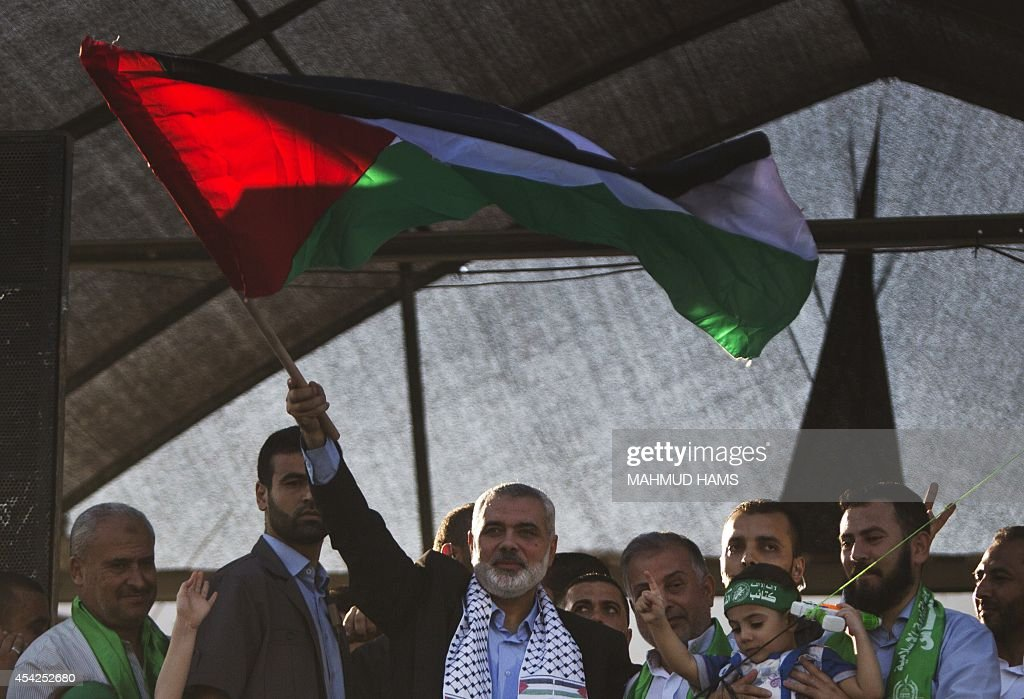 Hamas top leader in the Gaza Strip Ismail Haniya (C) waves the Palestinian national flag during a rally in Gaza City on August 27, 2014, following a deal hailed by Israel and the Islamist movement as 'victory' in the 50-day war. The agreement, effective from 1600 GMT on August 26, saw the warring sides agree to a 'permanent' ceasefire which Israel said would not be limited by time, in a move hailed by Washington, the United Nations and top world diplomats.